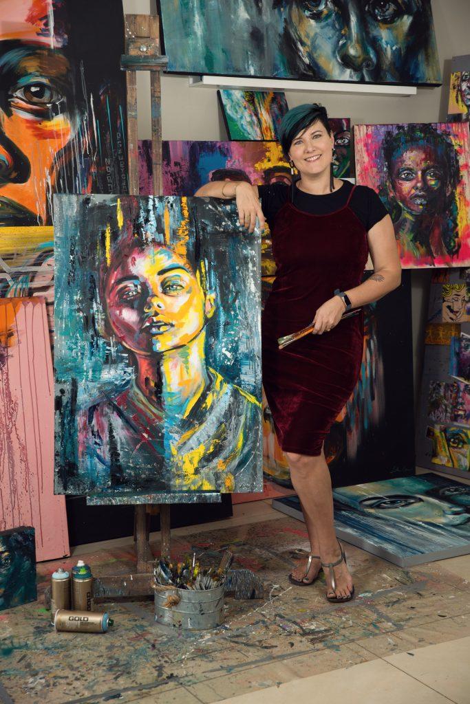 Artist Lillian Gray standing next to her easel